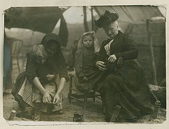 Paint Creek–Cabin Creek strike of 1912 - Mother Jones ties the shoelaces of a miner's child in the tent colony.