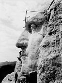Profile of stone face on mountainside, with 3 workers.