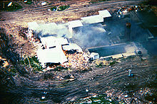 An overhead view from a helicopter of the Mount Carmel Center building. Large columns of smoke are arising from the left side of the building from a fire. One side of the building shows extensive damage. The building is surrounded by dirt paths.