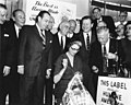 Mrs. Nelson Rockefeller sews a union label into a garment while Luigi Antonini, Charles Zimmerman, Robert F. Wagner, Herbert Lehman, Nelson Rockefeller, David Dubinsky and others look on. (5279149965).jpg