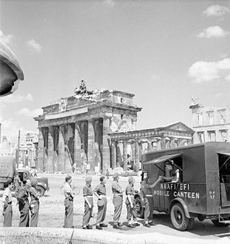 Navy, Army and Air Force Institutes - British soldiers queue for tea at NAAFI Mobile Canteen No. 750 beside the Brandenburg Gate, Berlin, July 1945. This van was the first mobile NAAFI to operate in Berlin
