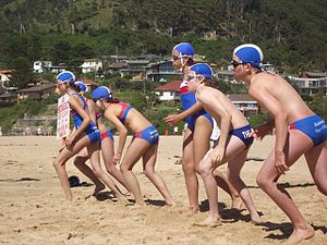Surf Life Saving Club - Under-12 aged nippers in start position before their swim in Stanwell Park, dressed in local SLSC uniform.