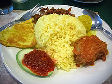 A dish of rice surrounded by various condiments
