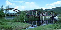 A bridge with three wooden arches, spanning a river