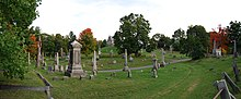A panoramic view of the cemetery; a dirt road pass in front of the view from right to left. At center is a grey church-like structure, surrounded on all sides by various sized grave stones.