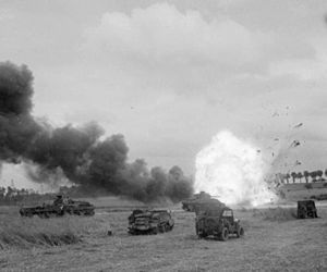 Operation Epsom - An ammunition carrier of the British 11th Armoured Division explodes after it is hit by a mortar round during Operation Epsom, 26 June 1944.