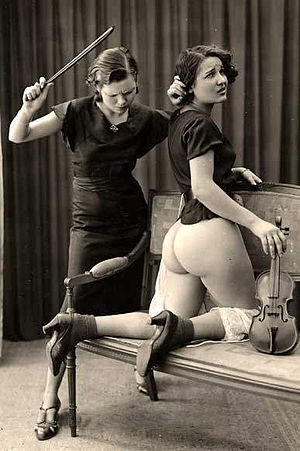 Dominatrix - A scene where both dominant and submissive are female, 1930. In this scene, the strict dominatrix has stripped the submissive and is caning her buttocks for not playing the violin properly. In BDSM such beating has to be consensual.
