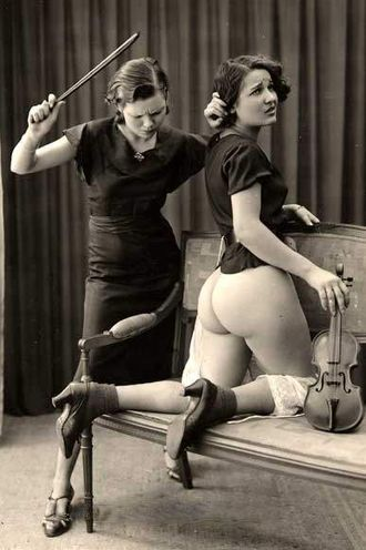 Dominatrix - A scene where both dominant and submissive are female, circa 1930s. A music teacher is caning the buttocks of a student with a violin bow.