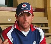 An English cricketer in a red, white and blue shirt and cap, with his tongue between his lips.