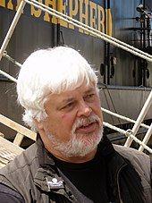 A heavyset man with white hair and a white beard, standing in front of a boat with the words «Shepherd» written on it in yellow paint