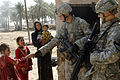 Pfc. Kurtis Tripp, 2nd Battalion, 5th Cavalry Regiment, 1st Cavalry Division, greets local Bini Ziad village children during a cordon and search operation at a village west of Baghdad, Iraq, Feb. 17, 2007.jpg