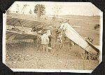 Photograph of a group of men and boys around a crashed Royal Flying Corps aircraft . (7980815673).jpg