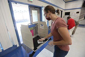 A poll worker sanitizes an election booth in Davis, California Poll worker sanitizes election booth.jpg