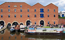 A brick-built warehouse with a canal in the foreground. There are barges on the canal and people sitting outside the warehouse.