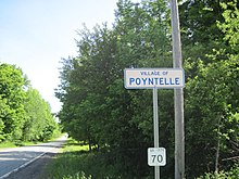 "An image of a white sign with blue lettering and border, reading ""VILLAGE OF/POYNTELLE,"" against a background of greenery."
