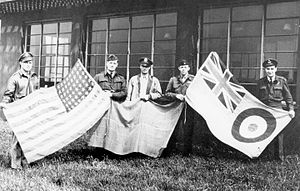RAF Goxhill -  British and American personnel hold up flags at the 496th Fighter Training Group base in Goxhill., 1944