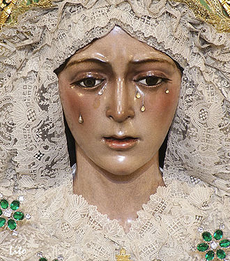Virgin of Hope of Macarena - A close-up on the face of the image. Later restorations enhanced  the cheekbones to masquerade the alleged stain on the cheeks. Note the five mariquillas or brooches donated by the bullfighter El Gallo.