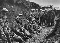 Black and white photo of two dozen men in military uniforms and metal helmets sitting or standing in a muddy trench.