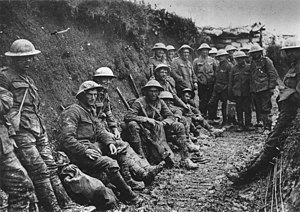 In a black and white photograph, 15 soldiers in standard uniform are leaning against a trench wall