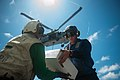 Sailors aboard USS Mobile Bay (CG-53) carrying package off flight deck with MH-60S Seahawk in background 121012-N-LV331-260.jpg