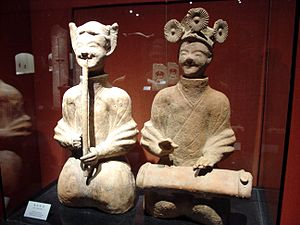 Music of China - Lively musicians playing a bamboo flute and a plucked instrument, Chinese ceramic statues from the Eastern Han period (25-220 AD), Shanghai Museum