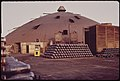 """Shell Casings Are Stacked Outside """"Domes."""" the Domes Are Notorious for the Lack of Air Circulation and the Heat Which Builds Up Inside. Le Tourneau Marathon Ammunition Plant 06-1972 (3703569189).jpg"""