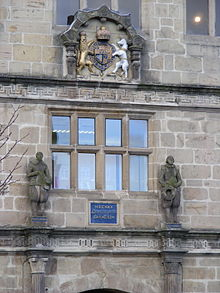 Two stone statues of Philomath and Polymaths in Elizabethan dress, on the original buildings; also featured on the contemporary school library
