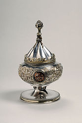 Silver gilt vessel with conical lid. It was intended for use as a ciborium. The vessel is decorated with foliate scrolls and medallions. The knob on the vessel's lid is in the shape of a bunch of grapes.