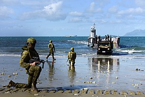 Colour photograph of three men wearing green military uniforms kneeling on a beach near a grey ship. A green truck is driving off the ship, and a large grey ship is visible on the horizon.