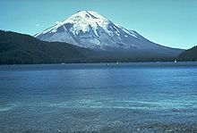 Conical mountain with snow near the top as seen from a lake