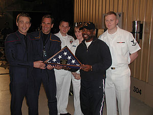 "Star Trek: Enterprise (season 2) - Three crew members of the U.S. Navy aircraft carrier Enterprise present a flag to Conner Trinneer, Scott Bakula and LeVar Burton on the set of ""First Flight""."