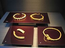 Three elaborate gold coloured torcs lie on dark red surfaces. A fourth torc is in two pieces.