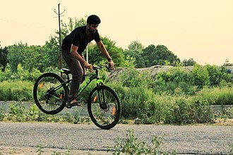 Stoppie - A Boy performing stoppie with a mountain bike.