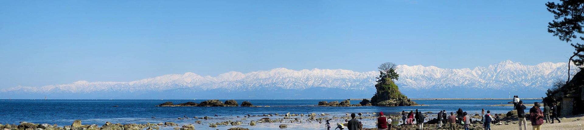 https://upload.wikimedia.org/wikipedia/commons/thumb/f/f5/Tateyama_Mountains_and_Onna-iwa_viewed_from_Amaharashi_Coast_20190309134344.jpg/1920px-Tateyama_Mountains_and_Onna-iwa_viewed_from_Amaharashi_Coast_20190309134344.jpg