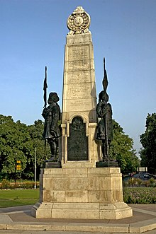 "A cream-coloured stone obelisk bearing names rises into a blue sky. Above its base plinth is a large, black plaque bearing the words ""Their names liveth for evermore"" and ""Teen Murti"". On either side on its plinth is a statue of a turbaned man in military uniform holding aloft a weapon with a flag at its top. Behind the obelisk is a garden with pink flowers and trees, and a road recedes into the distance."