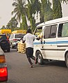 Traffic Hawker in lagos chasing after a bus.jpg