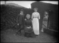 Two unidentified women and a boy in a garden. ATLIB 283798.png