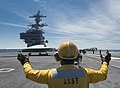 U.S. Navy Aviation Boatswain's Mate (Handling) 3rd Class Audley Campbell directs a Navy X-47B Unmanned Combat Air System demonstrator aircraft as it taxis on the flight deck of the aircraft carrier USS George 130514-N-FU443-679.jpg