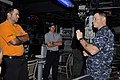 U.S. Navy Lt. j.g. Ryan Schwartz, right, a combat information center officer aboard the guided missile destroyer USS Chung-Hoon (DDG 93), explains his workspace to Professional Golfers' Association of America 140108-D-PJ759-070.jpg