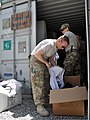 U.S. Navy Petty Officer 2nd Class Todd Gilbert, front, and Army Sgt. 1st Class Mary Good, both with Combined Joint Interagency Task Force 435, sort boxes of clothing donations for an Operation Outreach 130728-F-JL359-011.jpg