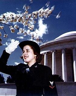 U.S. Navy WAVE Specialist (Photographer) 3rd Class saluting, cherry blossoms near Jefferson Memorial, Washington, D.C., World War II