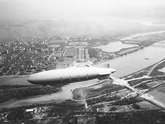 """Columbia Island (District of Columbia) - The dirigible USS Akron flies over Columbia Island in 1931. Below and to the right of the airship's tailfins is the island, on which extensive construction is under way on the """"great plaza"""", axial roads, Boundary Channel Bridge, and Memorial Drive. Note the lack of any bridges to the north (left in this image)."""