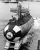 Black-and-white photo of submarine being slid into water during launching. Dozens of people are standing on top of it.