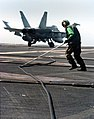 US Navy 040325-N-6213R-128 An Aviation Boatswain's Mate keeps the arresting cable on track as it is retracted following the recovery of an F-A-18C Hornet.jpg