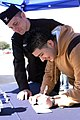 US Navy 050228-N-3750S-001 Journalist 2nd Class Jason Heaver, left, Navy Recruiting District Houston Public Affairs Officer (PAO), helps high school senior, Celso Baez III, fill out an informational form.jpg