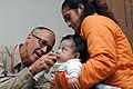 US Navy 070809-N-7088A-085 Cmdr. Craig Martin, attached to Military Sealift Command hospital ship USNS Comfort (T-AH 20), examines a baby at the Jose F. Sanchez Carrion School.jpg