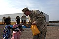 US Navy 070906-N-3931M-013 U.S. Navy Lt. Brian Baker, attached to the Combined Joint Task Force-Horn of Africa (CJTF-HOA), presents a gift to a local student during a school dedication ceremony.jpg