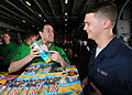 US Navy 080726-N-9898L-007 Aviation Electrician's Mate 3rd Class Stephan Riggs shows Ship's Serviceman Seaman Kevin Simak a note attached to a box of Girl Scouts cookies.jpg