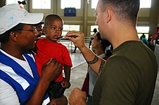 US Navy 081015-N-4515N-198 Canadian Army Pvt. David Pivato, embarked aboard the amphibious assault ship USS Kearsarge (LHD 3), administers an anti-parasitic medication to a young Dominican boy.jpg