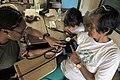US Navy 090421-A-0759M-098 Hospital Corpsman 1st Class Donna Moreland, examines a woman during a medical civic action project supporting Balikatan 2009 at Nakar Elementary School.jpg